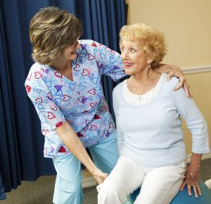 Physical therapist helps a senior woman exercise using a pilates ball.